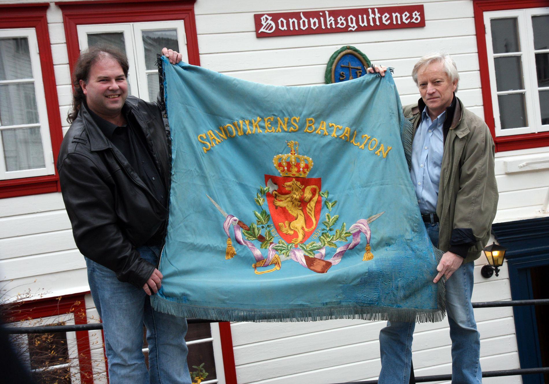 FIKK IGJEN FANEN: Frantz H. Dueland (t.v.) og Kjell Lervik i Sandviksguttenes forening med fanen som har vært borte siden 1990.