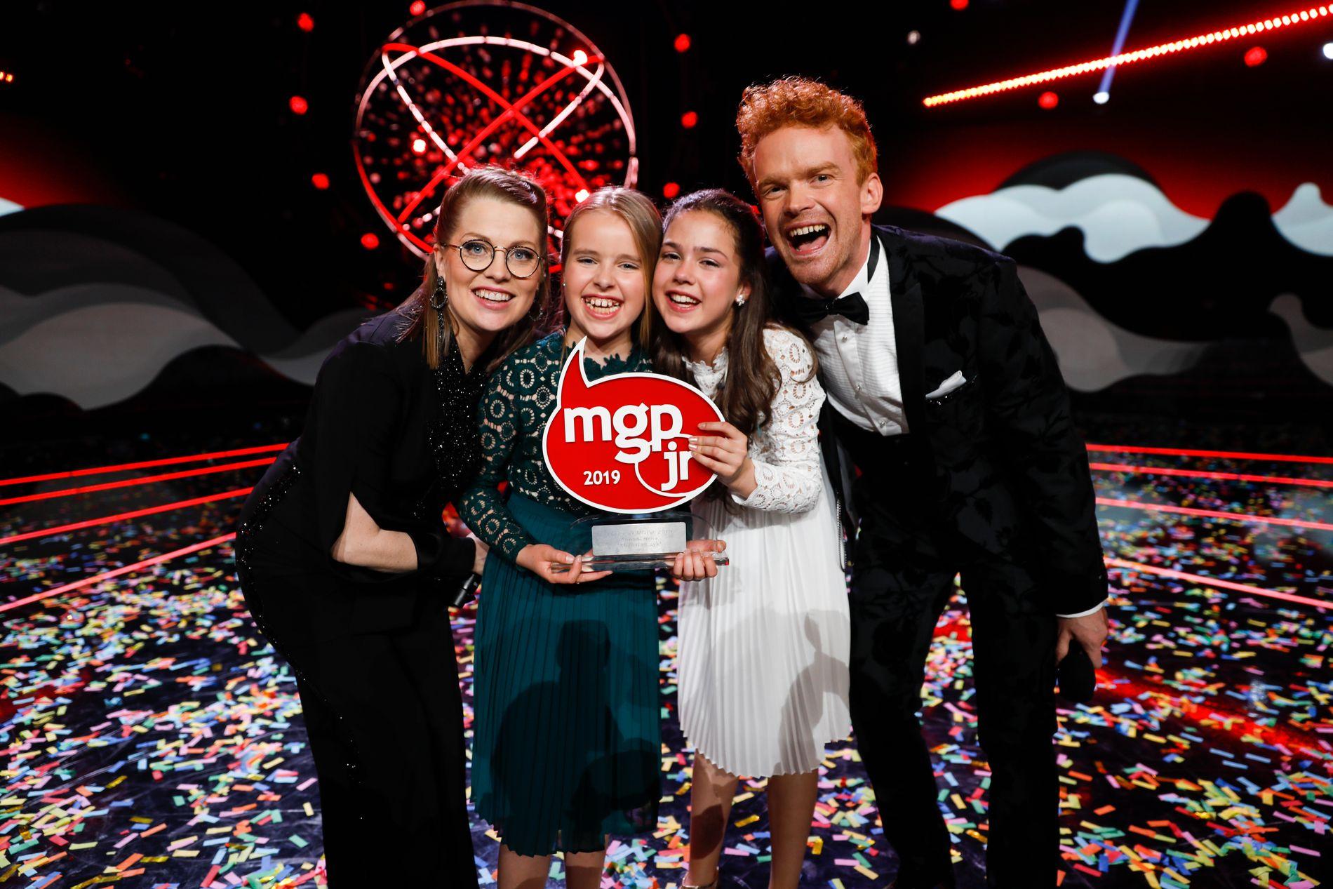 PÅ KOENGEN: Anna og Emma vant årets MGPjr med låten «Kloden er syk». Til venstre står programleder Programledere Sigrid Velle Dypbukt og til høyre Mikkel Niva.