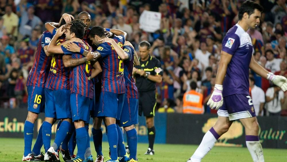Barcelona's players celebrate David Villa's goal against Osasuna goalkeeper Andres Fernandez during their Spanish first division soccer match at Nou Camp stadium in Barcelona September 17, 2011.   REUTERS/Gustau Nacarino  (SPAIN - Tags: SPORT SOCCER)