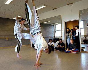 ANNERLEDES 40-ÅRSFEIRING: Langhaugen skole har rukket å bli førti år. Elever og lærere har feiret hele uken, og i går ble timeplanen oppløst til fordel for valgfrie kurs. Noen av elevene underviste, og her er Ken Hedin Kalvik (t.h.) og Kim-Andreas Herøy (16) i aksjon på sitt populære capoeira-kurs.