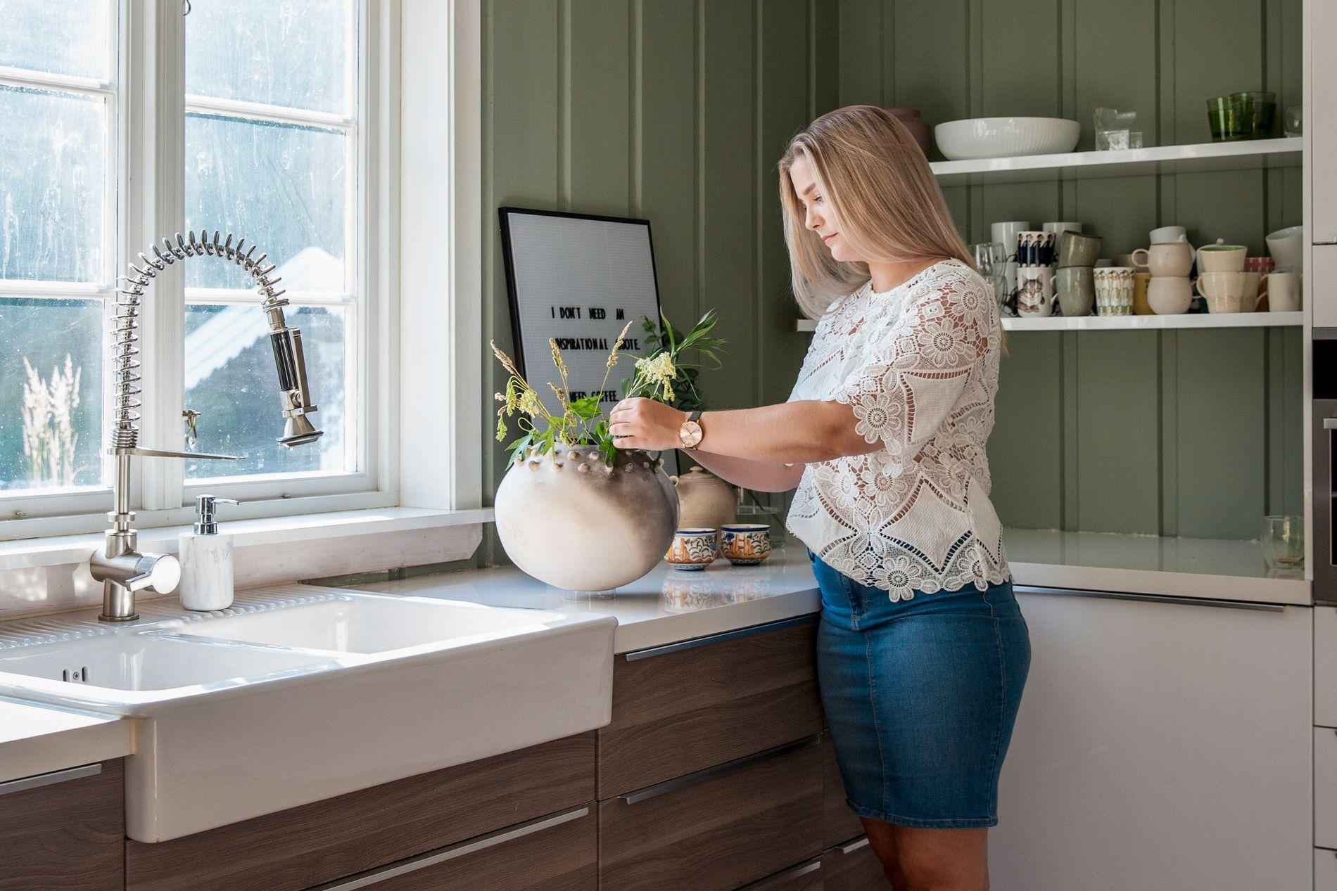 Alice Bratås er kreativ og liker å skape. Her er hun på kjøkkenet med en vase hun har laget selv av leire, brent i selvbygget teglsteinsovn.