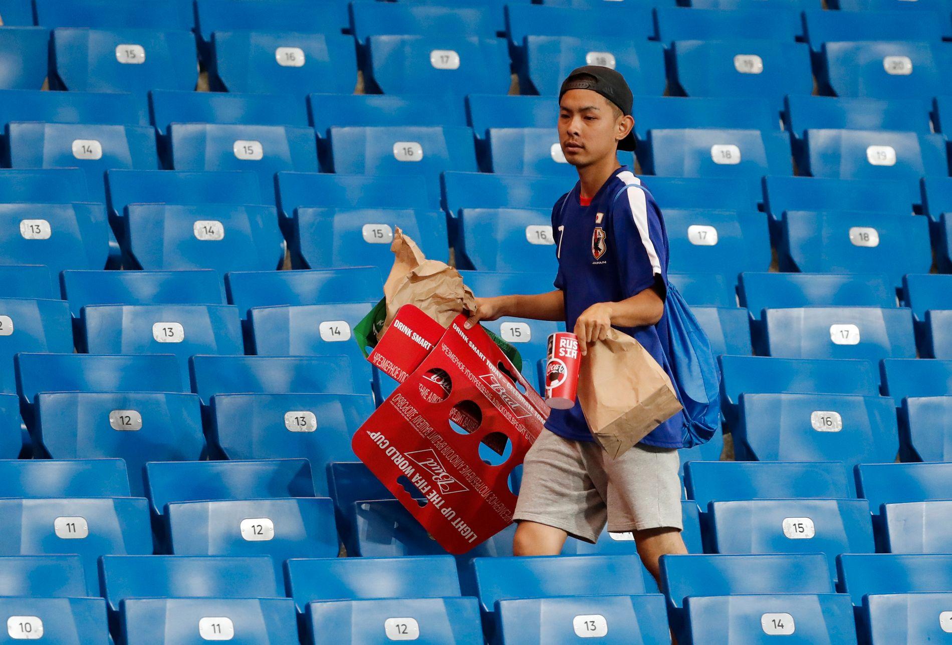 Her plukker en japansk supporter opp søppel etter tapet for Belgia.