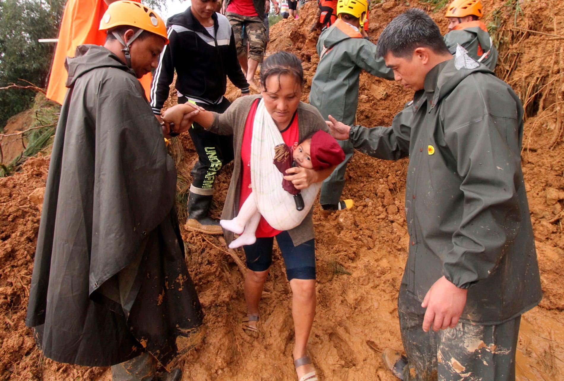 FÅR HJELP: Redningsarbeidere bistår en mor og hennes barn som evakueres etter et kraftig jordskred i Itogon i Benguet-provinsen nord på Filippinene. Jordskredene i Benguet har krevd over 30 menneskeliv.
