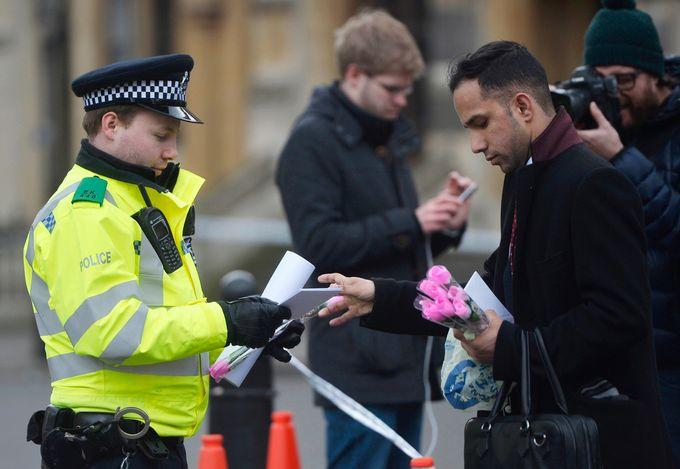 ROSER: En mann deler ut innpakkede roser til politifolk på åstedet for London-terroren i mars.