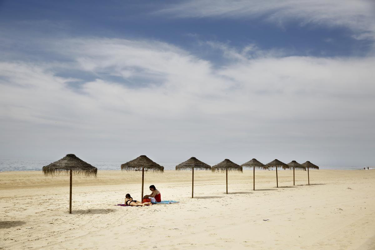 ØDE ØY: Ilha Deserta, navnet betyr øde øy, ligger ute i havgapet med det røffe Atlanterhavet skyllende inn over seg. Noen få strandparaplyer er satt opp langs den 11 kilometer lange sandstranden.