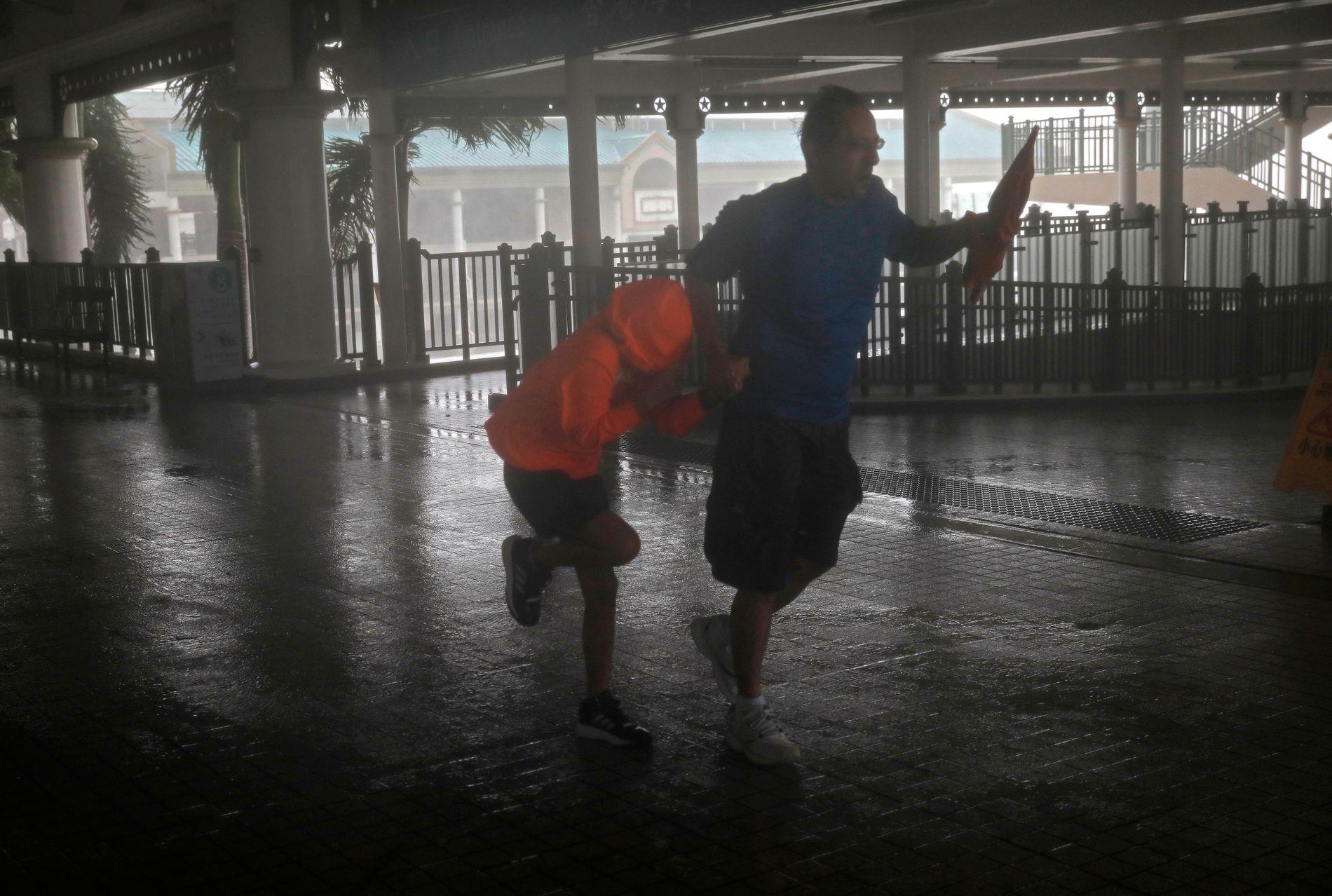 TROSSER VINDEN: En mann og ei jente trosser sterk vind forårsaket av tyfonen Mangkhut ved Victoria Harbour i Hongkong søndag.