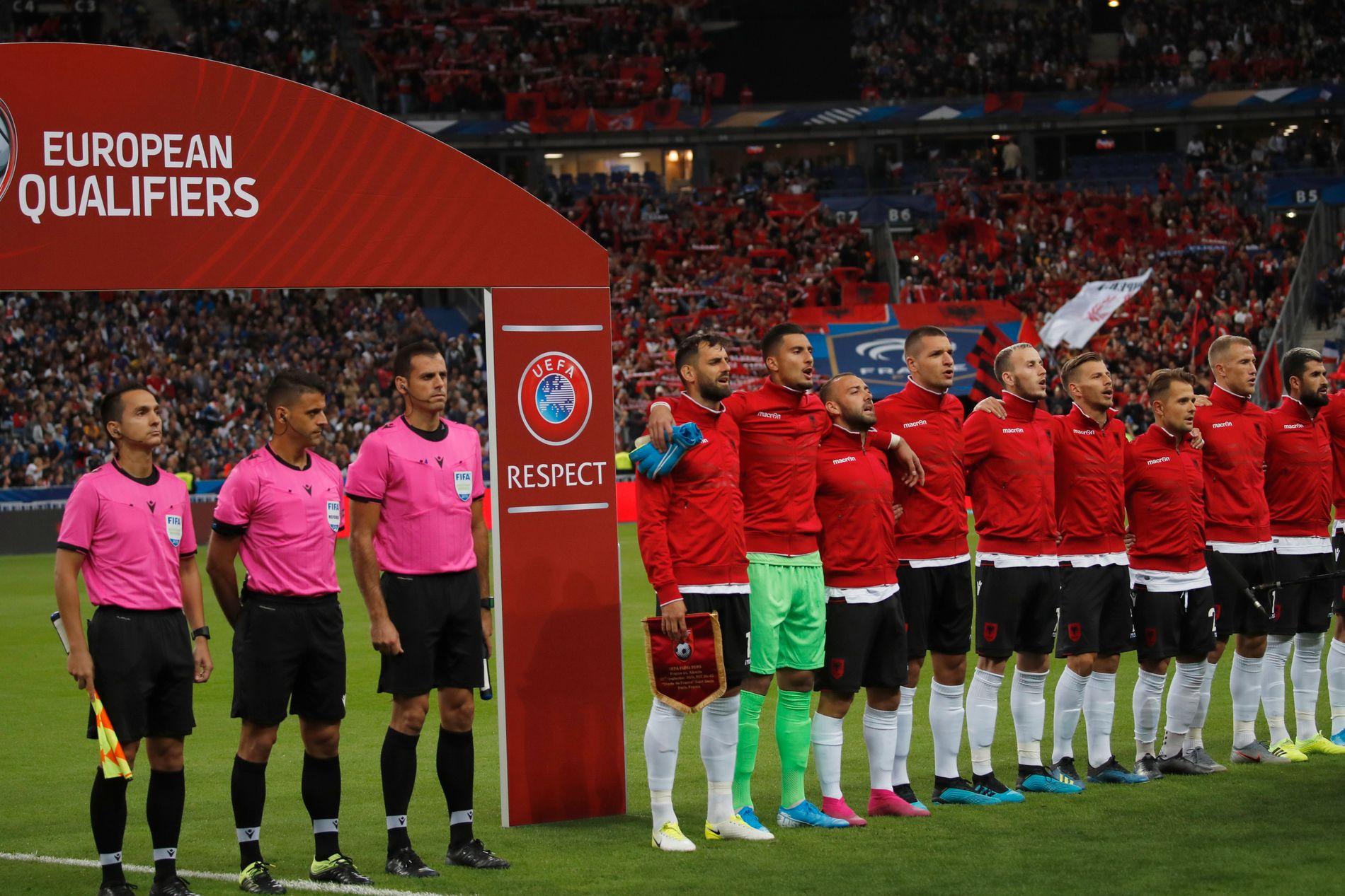 Dommere og det albanske fotballandslaget lytter og synger under den albanske nasjonalsangen, etter å først ha hørt nasjonalsangen til Andorra, og deretter fått en unnskyldning rettet til Armenia.