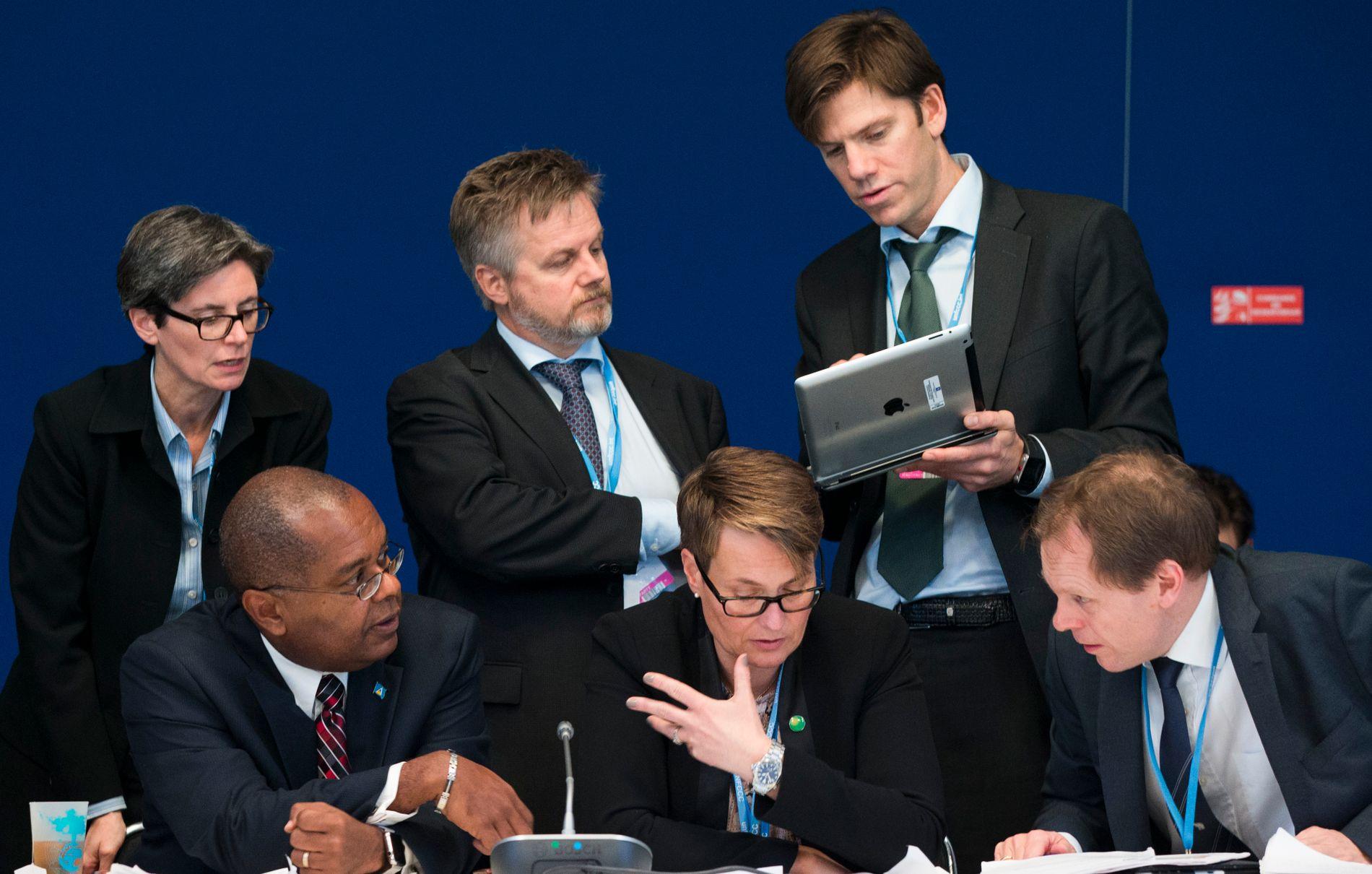 INTENS FASE: Klimaminister Tine Sundtoft leder forhandlingene om ambisjonsnivå i den ny klimaavtalen. Her er hun flankert av minister-kollega James Fletcher (Saint Lucia) og Norges forhandlingsleder Aslak Brun (til h.). Bak står medlemmer av det norske forhandlingsteamet i Paris.