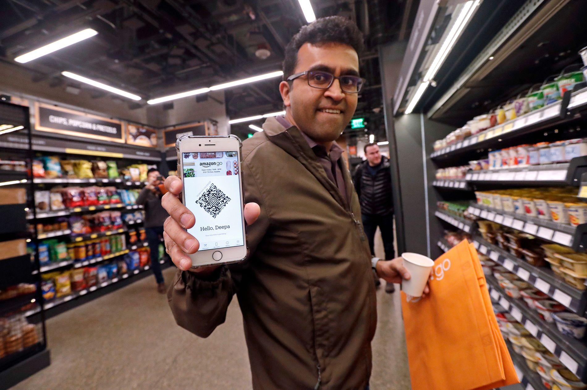 KJØP&GÅ: Ein tilsett i Amazon Go-butikken i Seattle viser mobilappen du treng for å kome deg inn i butikken. Ei mengde kamera og sensorar følgjer med på kva du tek frå hyllene, og trekkjer betalinga frå Amazon-kontoen din.
