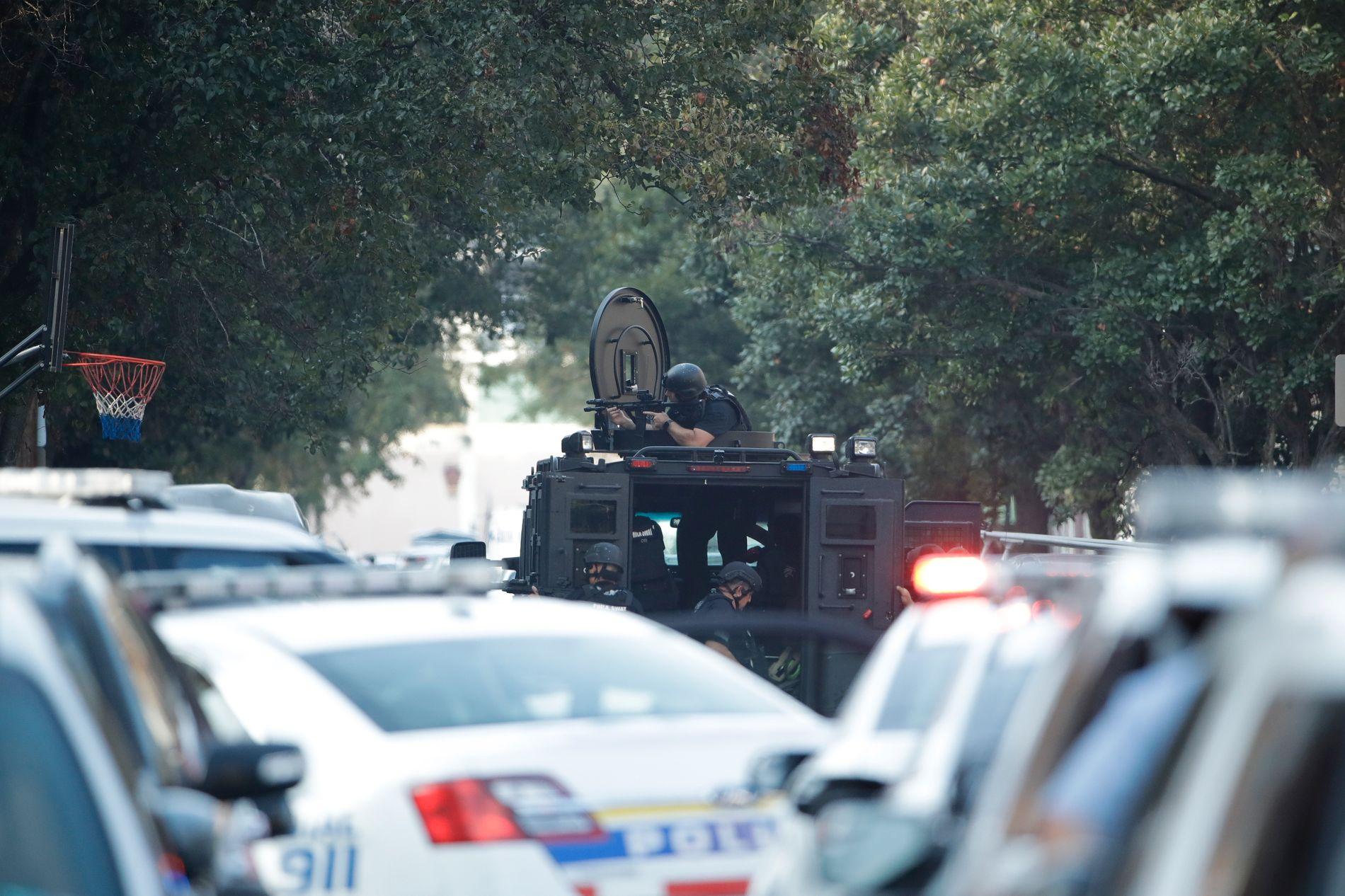 Politiet tar oppstilling utenfor bygget der gjerningspersonen forskanset seg. Foto: Matt Rourke / AP / NTB scanpix