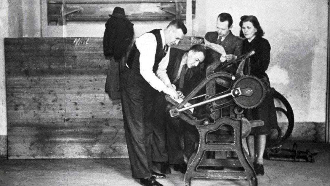 MANGE DELTOK: Produksjon av en illegal avis i bergensområdet. Avisens navn og bildets aktører er ukjente. Fotografiet er fra en rekonstruksjon etter krigen. ARKIVFOTO: UBS BILLEDSAMLING