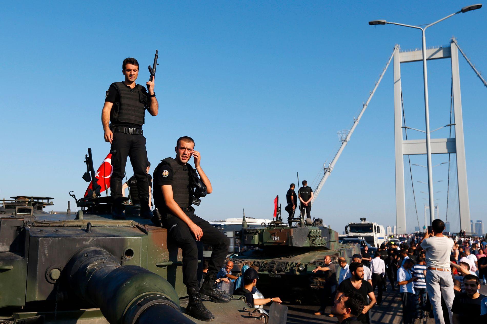 OVERGA SEG: Politimenn står på toppen av en tanks etter at tropper som var involvert i kuppet måtte overgi seg ved Bosporusbroen i Istanbul.