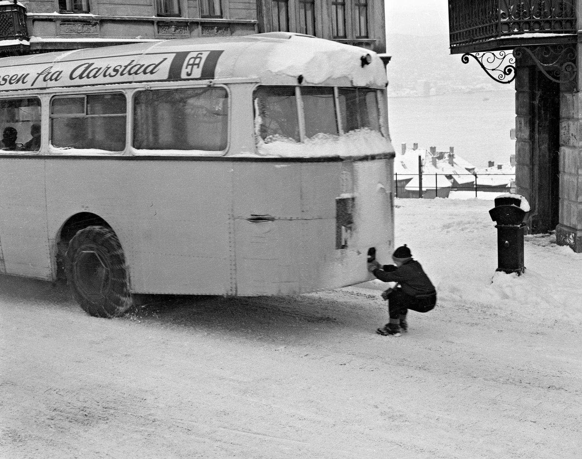 KJANKET: Kjanking var et utbredt vintersport før i tiden. Her går det unna bak en buss i Haugeveien. Gøyere kunne det ikke bli.