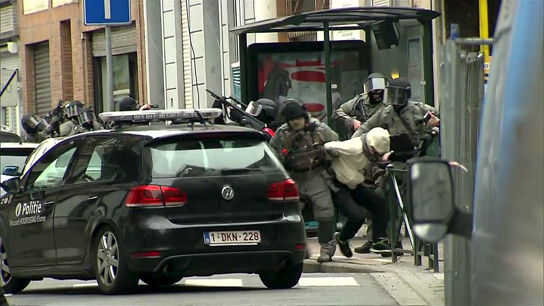 Belgisk politi tar med seg en mistenkt ut fra leiligheten der Salah Abdeslam ble pågrepet fredag.