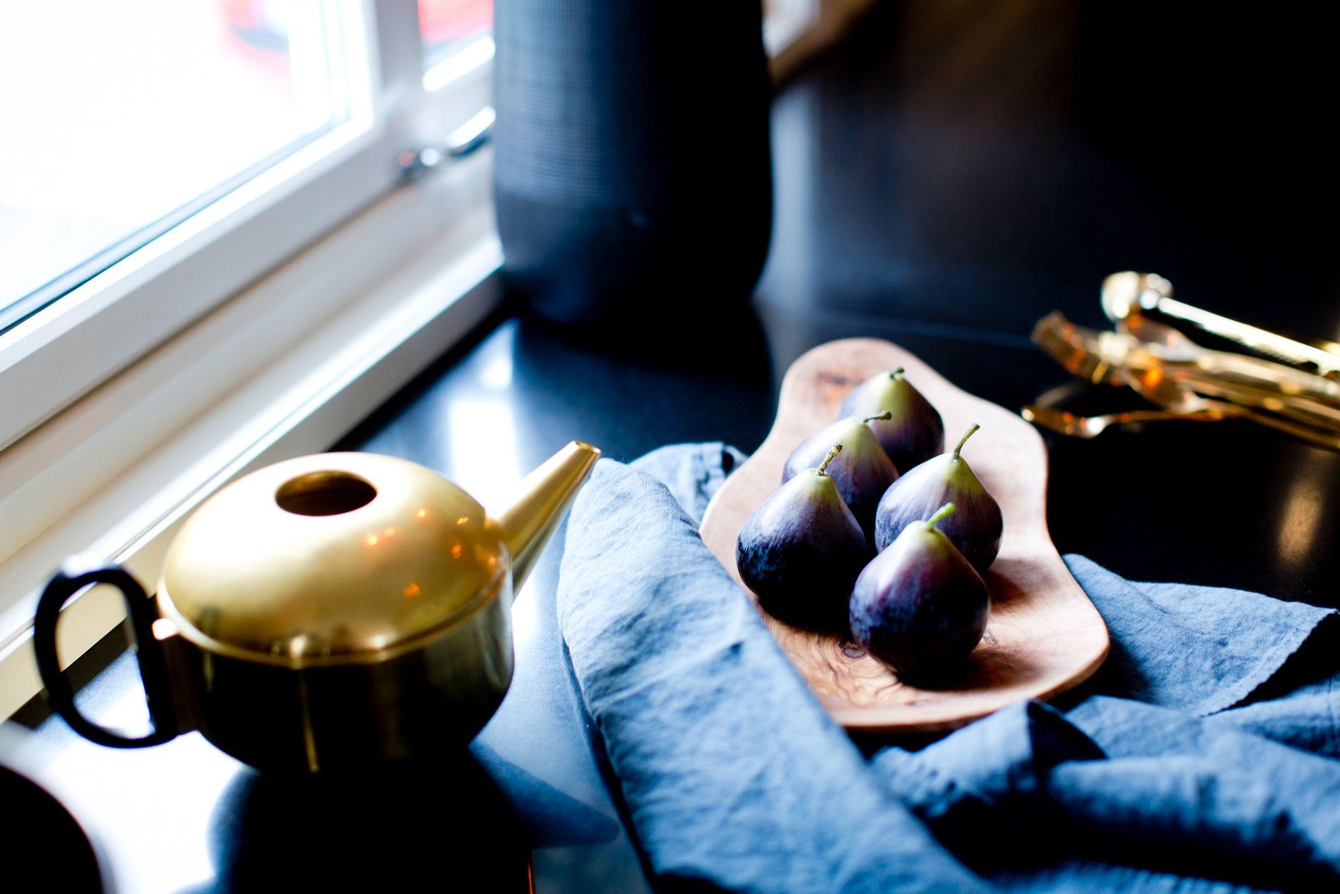 MØRKE FARGER: Nina Oppedal inspireres av dramatiske og mørke farger, men kan ikke ha det helt mørkt hjemme hos seg selv. Hun tar det gjerne igjen i detaljene, som her på kjøkkenbenken hvor svart benkeplate pyntes opp med en svart vase, svart kjøkkenmaskin, et trefat, en messingkanne og messingbestikk.