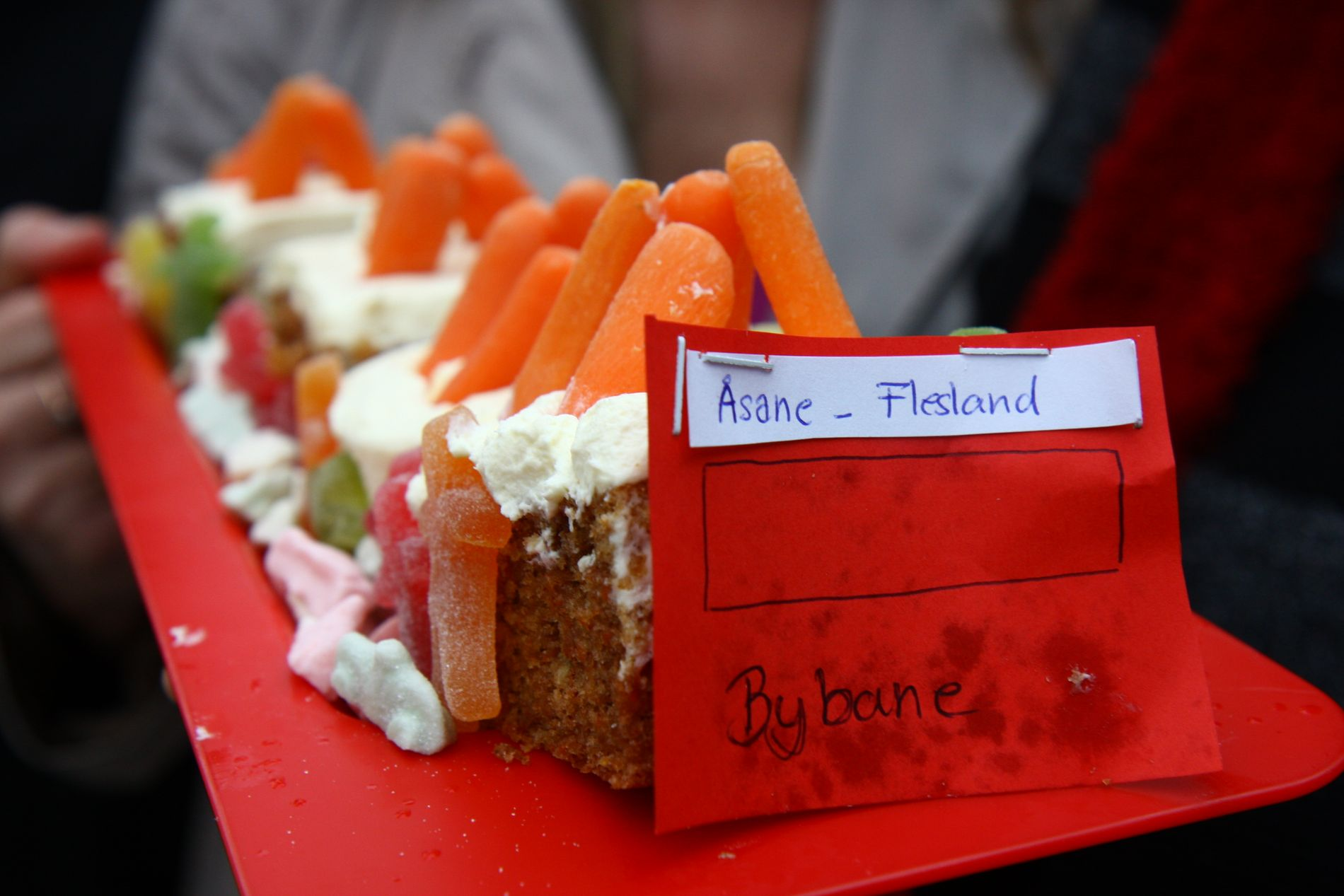 SYMBOLSK: Gulrøttene symboliserer belønningsmidlene Bergen kan få. Kakefatet er også fult av små sure biler. Kaken ser ut til å gå i rute helt fra Åsane til Flesland.FOTO: RUNE STØLÅS