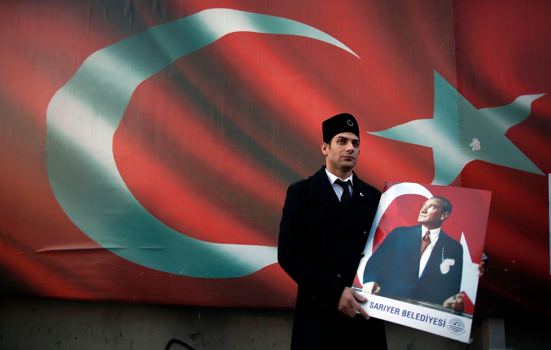 PROTEST: Den demonstrant utenfor redaksjonslokalene til den nedstengte opposisjonsavisen Cumhuriet denne uken bærer en plakat av den tyrkiske landsfaderen Mustafa Kemal Ataturk. Minst 13 seniormedarbeidere i avisen skal være fengslet.