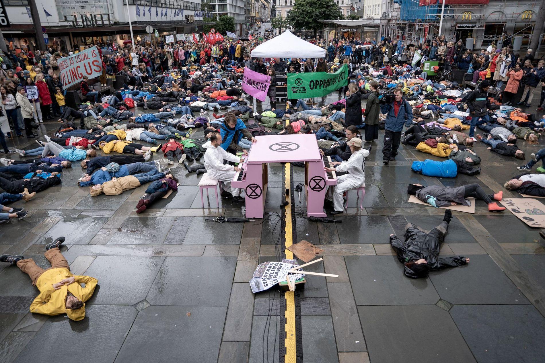 KLIMAAKSJON: Ungdommene trosset regnet og la seg ned på bakken på Torgallmenningen fredag 30. august.