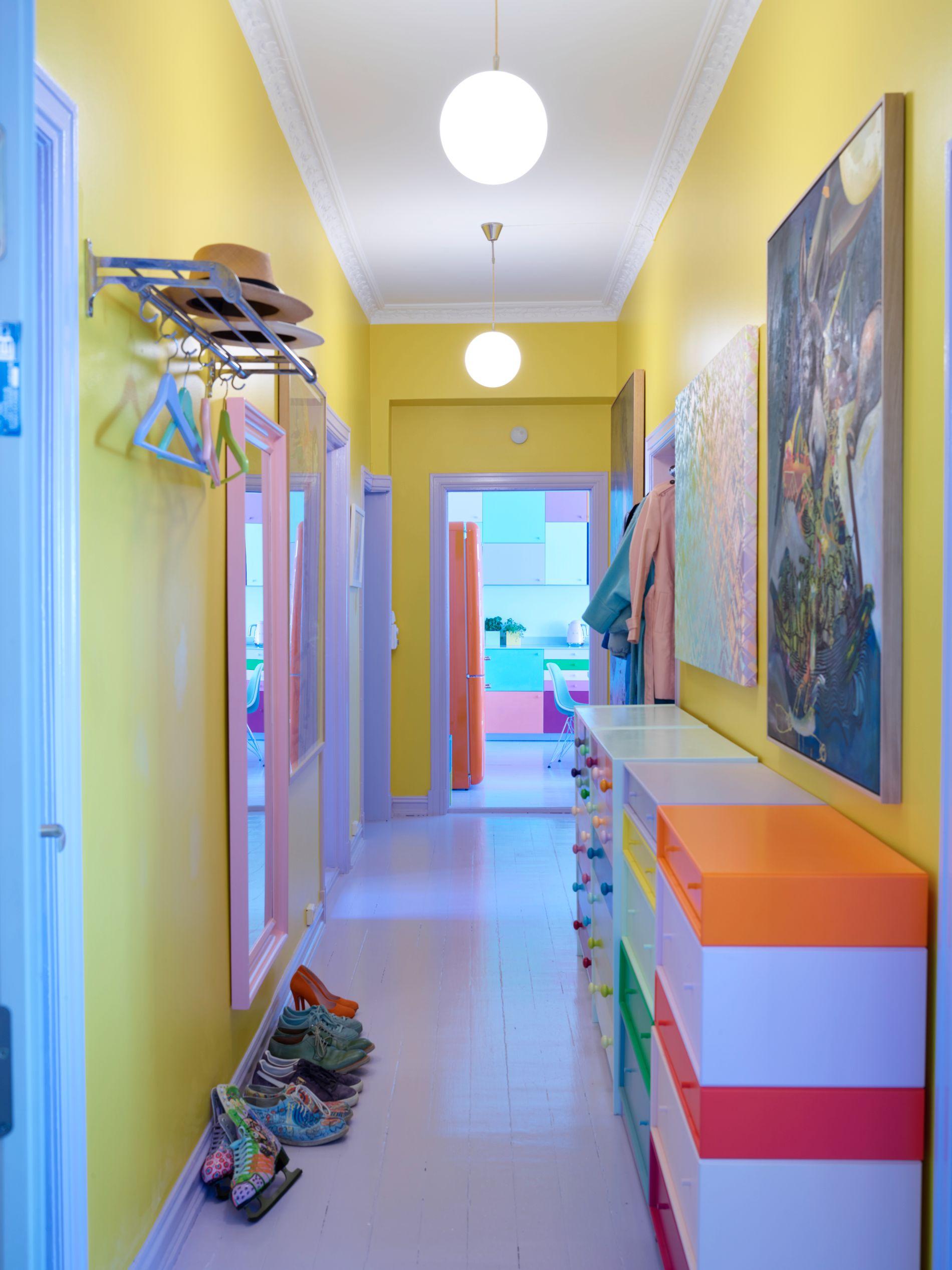 GUL GANG: Du kan ikke unngå å bli i godt humør når du åpner døren og møtes av denne lysende gule gangen. Ulike kommoder med mangefargede skuffer og et stort rosa speil gjør inntrykket komplett.