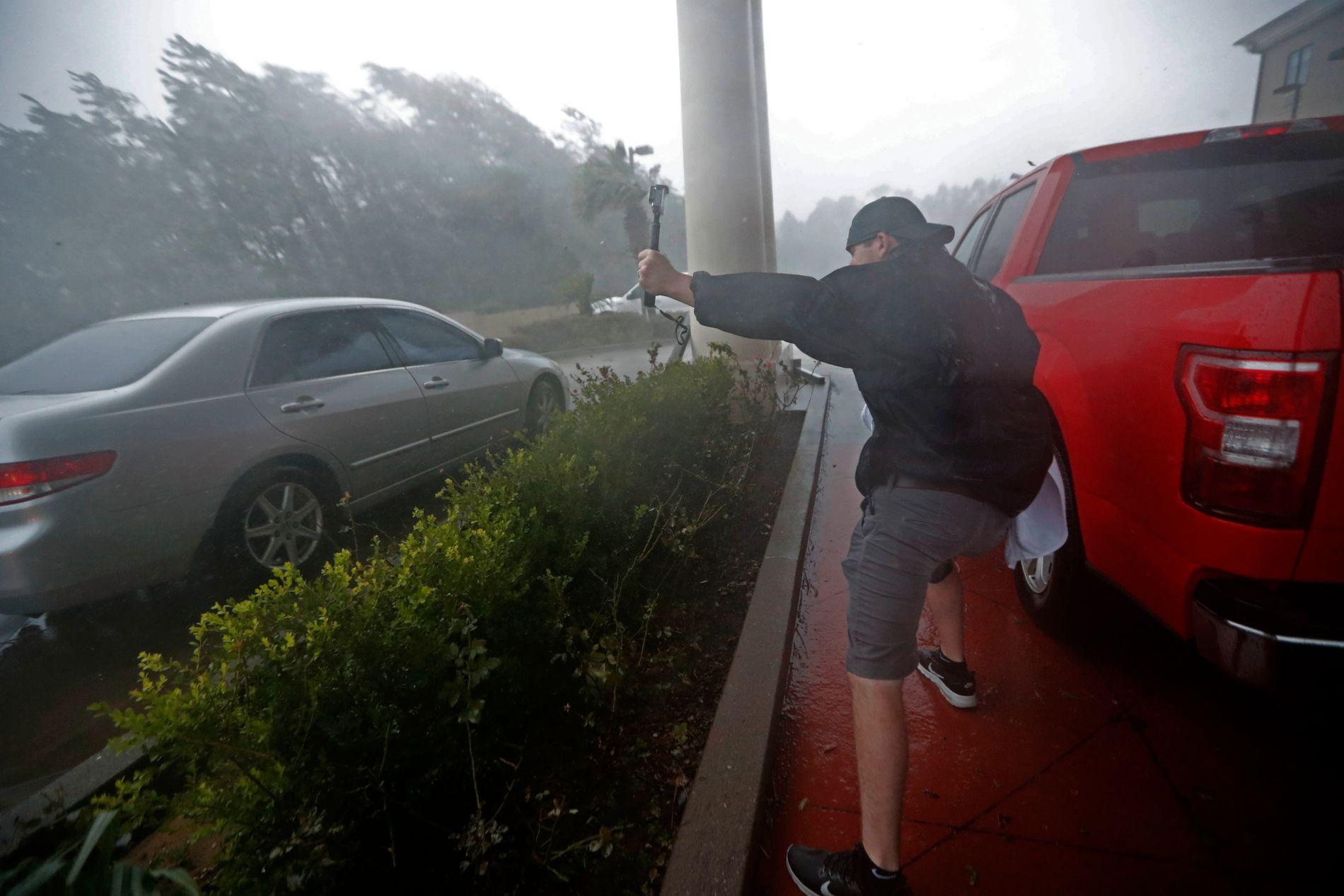 FEIDE INNOVER FLORIDA: En mann er ute og filmer under uværet i Panama City i Florida.