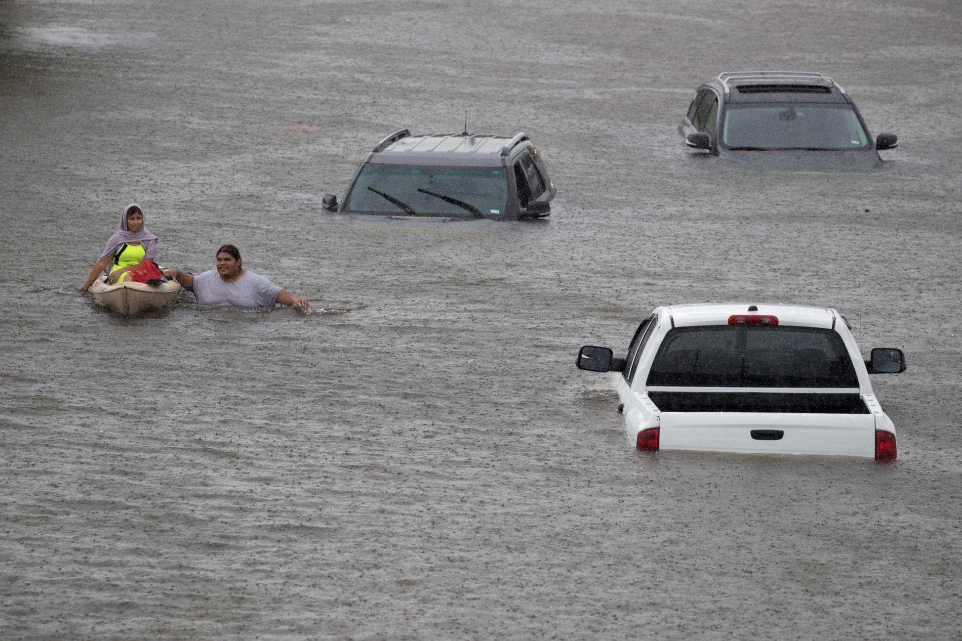 TEXAS I GATENE: Houston fikk hard medfart under orkanen Harvey i slutten av august. Her blir Gloria Garcia reddet av Jesus Rodriguez i de oversvømte gatene.