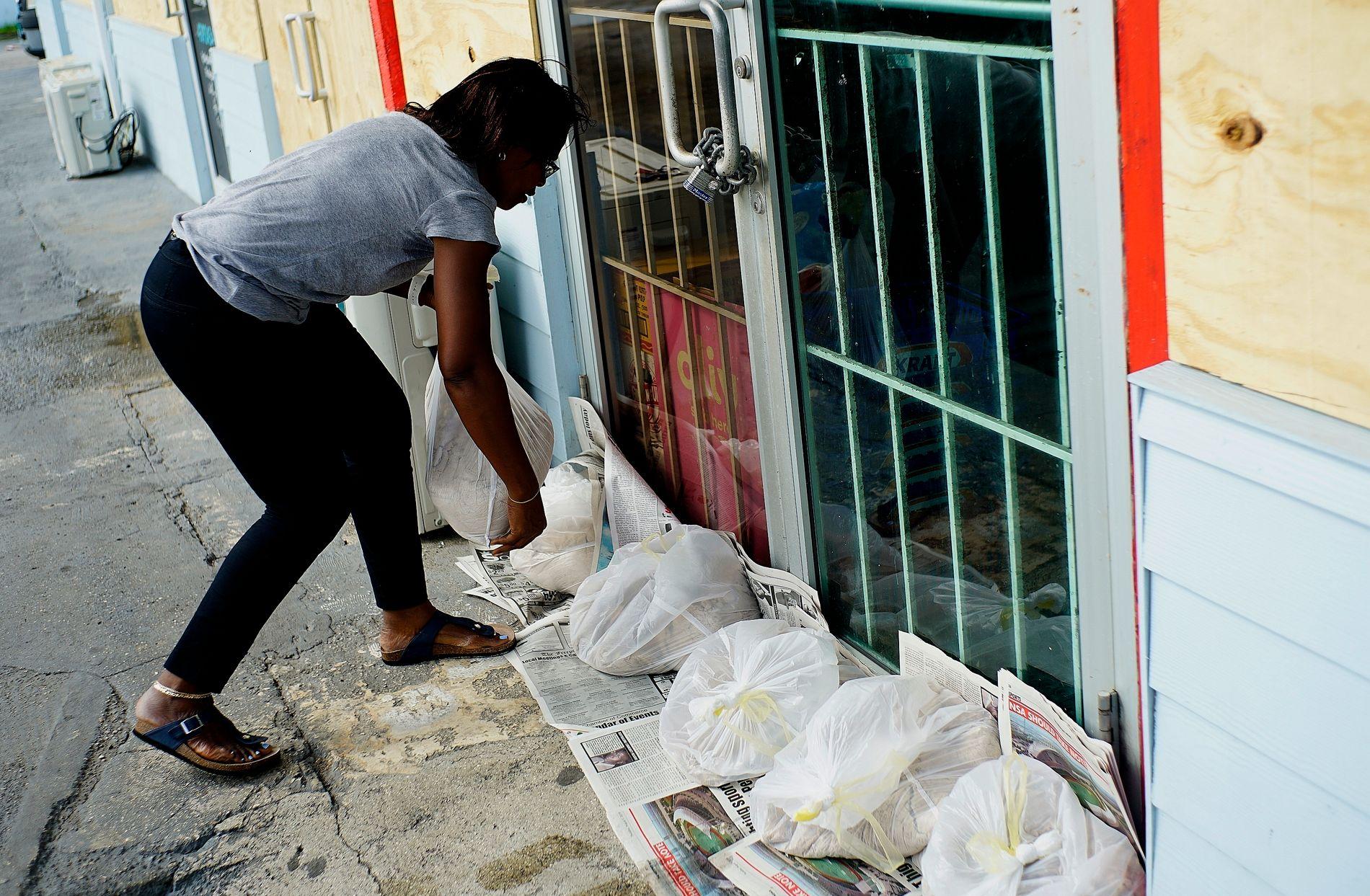 BESKYTTER BUTIKKER: Yolande Rolle putter sandsekker utenfor butikken sin i Freeport på Bahamas.